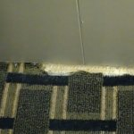 Ripped carpet by door, lets in a very cold draft in winter