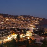 Dusk over funchal from our balcony .