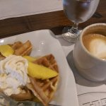 Enjoying a fresh mango waffle and double-shot mug of cappuccino.