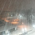 View over square outside & disco bar. Snowing hard.