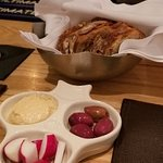 Bread,hummus, radishes, and olives.