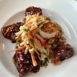 General Tso's chicken over fried rice, topped with Asian slaw