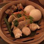 Dim Sum Basket-Pork pot stickers, shrimp siu mai, cha su bao and pork siu mai steamed on a banan