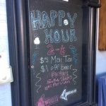 Happy Hour board visible from sidewalk in complex