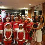 Cute group of girls together with Santa clause singing and dancing at Christmas night