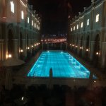 The hotel swimming pool at night with the city in the distance