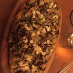 Flatbread with shitake mushrooms, arugula, pesto, and red onion.