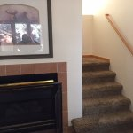 Condo's fireplace and stairs to upper level