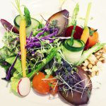 Fresh salad, baby vegetables, young aromatic herb shoots, dried fruits with tomato&yuzu vinaigre