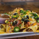 ~Nachos!~ Layers of our house made nacho cheese sauce, topped with all sorts of goods!