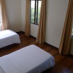 2nd bedroom with 2 single beds and wooden floors.