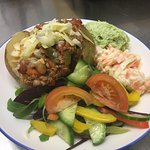 Jacket potato with chilli, cheese, guacamole, coleslaw and salad