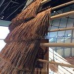 Display showing attachment of grass bundles to wooden hut framework