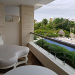Day bed, small table, and jacuzzi are all located within a balcony view