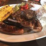 Grillteller mit verschiedenen Fleischsorten, Maiskolben und Ofenkartoffel