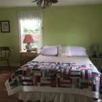 Green room with queen bed, an alcove with a twin bed & ensuite, view of ocean and small desk are