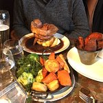 Sunday roast with Yorkshire pudding, side of vegetables and sweet potato wedges