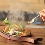 Hot sizzler comprising of samosa, lamb rack and charcoal chicken served on a bed of green salad.