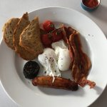 Breakfast, toast, sausage, bacon, poached eggs, pudding, tomatos