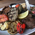 large mixed grill platter featuring beefteki, lamb chops, gyro, grilled veggies, and more
