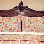 Antiques headboards and luxurious linens make for a restful sleep