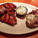Baby back ribs platter, with a loaded baked potato.