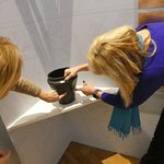 Visitors interact with a copy of a 5,000 BC drinking vessel on display.