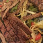 beef and vegetables on a sizzling platter