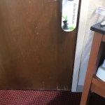 Room door with peeling veneer and something splattered on it.