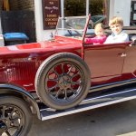 Friendly visitor with old car outside pub invited my kids to sit in it for a photo.