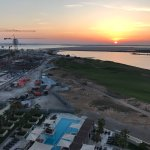 Pool, golf, beach and construction at sunset