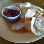 Homemade potato chips with salsa.
