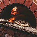 Настоящая неаполитанская пицца, приготовленная в дровяной печи.