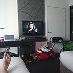 """Dwoje Gości odpoczywa i ogląda serial """"Korona Królów"""" z laptopa połączonego z telewizorem..."""