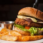 Our homemade avocado chiken burger with french spicy fries.