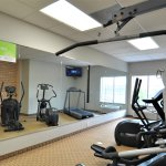 Exercise room equipped with machine weights and cardio equipment.
