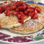 Special - White chocolate cheese cake pancakes topped with fresh strawberries & powdered sugar