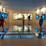 Sob o piso de vidro uma maquete gigante mostra o relevo e a geografia da região