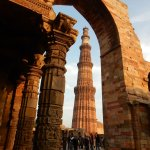The Qutub Minar framed by adjacent archways and pillars.