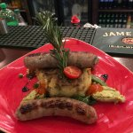 Pork, Guinness & balsamic sausages with crushed potato cake, curly kale,red pepper pesto & pea p