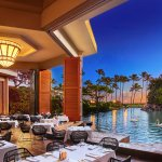 Our restaurant overlooks a lagoon, with views of a cascading waterfall and stunning sunsets.