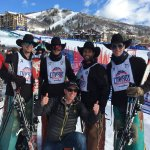 Ski valet, Bill, poses with some cowboys after they make it down the Cowboy Downhill safely.