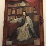 Nun in a library wearing a painting.