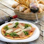 Pizza de Rucula y Prosciutto: Arugula, prosciutto y finas laminas de parmesano