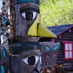 Totem pole by a cabin.