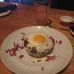 Asian burger over sushi rice Wasabi queso with an egg sunny side up
