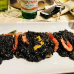 Risotto with squid ink, served with gold leaf and raw shrimp. This dish has to be ordered for tw