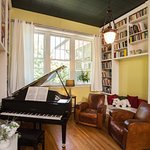 The ceiling-high Sweet Biscuit Inn library with baby grand piano