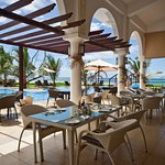Day-time dining by the pool, beachside at Le Cafe
