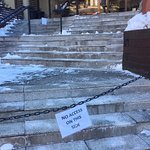 Front steps - cracked pavement, covered in ice and half of the stairs are cordoned off as not sa